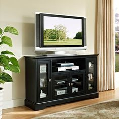 This stylish black wood TV stand will enhance the classic style of a living room or bedroom while it supports your TV. Glass-fronted doors hide your DVDs, DVD players, remotes, and other TV accessories. The stand measures 33' high and 52' wide.