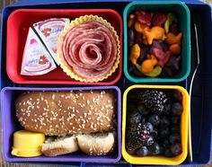 """Laughing Cow cheese wedges, a salami """"rose"""", goldfish crackers, blueberries and blackberries, a whole wheat hot dog bun and a little tub of strawberry jam."""