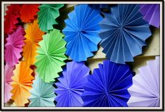Cardstock paper fan rounds as a backdrop for a rainbow birthday party