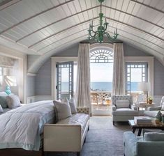 In the master bedroom, a boat-like bow ceiling sits within a dutch gambrel roof. The antique mirror above the fireplace conceals a TV; beyond the expansive Palladian window, a small balcony faces the ocean. My dream bedroom 😍 Dream Master Bedroom, Home Bedroom, Bedroom Decor, Bedroom Ideas, Bedroom Interiors, House Interiors, Bedroom Designs, Bedroom Lighting, Attic Master Suite