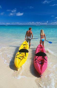 Couple with kayaks at Lanikai Beach on the windward side of Oahu