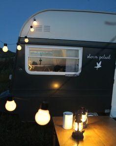 vivre en caravane, façade en blanc et noir, guirlande lumineuse pour décorer l'extérieur