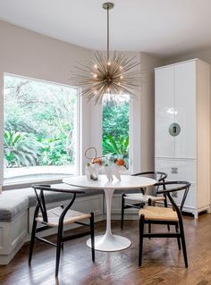 An Arteriors Zanadoo Chandelier hangs over an Ikea Docksta Table seating Hans Wegner Wishbone Chairs and a white dining bench placed under a bay window framed by cream colored walls, as a white lacquered chinoiserie china cabinet sits against a wall to the side of the table.