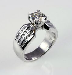 Contemporary platinum engagement ring with 3 rows of channel set diamonds
