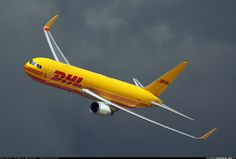 A DHL B767-3JHF Banking on display at Fairford in England with gray clouds as backdrop.