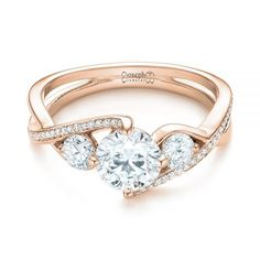 This elegant engagement ring features a round brilliant cut diamond prong set at the top, with a round diamond on either side, and bright cut set diamond accents lining one strand of the split rose gold shank. Designed and created by Joseph Jewelry   Seattle, WA   Bellevue, WA   Online   Design Your Own Engagement Ring   #engagementring #rounddiamondengagementrings
