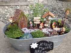 """My homemade fairy garden that I entered into the Kitsap county fair 2015. I made the house out of a cardboard box with sticks, pinecones, and moss. The wishing well is a toilet paper roll with rocks and sticks glued to it. The path is made out of sea glass that I've collected over the years. I made the signs out of wooden skewers and Popsicle sticks. I also put in some vintage dwarf figurines that I got from my grandmother. Had lots of fun making it! By the way, I misspelled haven on…"