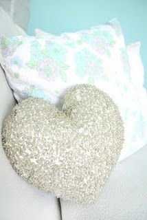 Heart sequin cushion in a bright blue living room