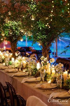 The reception space is transformed into an enchanted garden overflowing with white floral arrangements, candlelight and lush green trees sprouting from tables. Wedding Decorations, Floating Candles, Candle Holders, Centerpiece:
