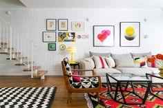 המדרגות לקומת הגג מתחילות ליד הספה. הקיר הגדול חופה בלבנים שנצבעו בשלוש שכבות של סיד כדי לבטל זיקה לסגנון כפרי, ועליהן נתלתה קומפוזיציה של יצירות אמנות (שתי הבולטות שבהן של האמן הגרפי Genis carreras). מנורה על רגל צהובה בוהקת במרכז (צילום: שירן כרמל)