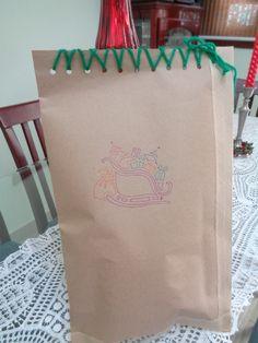 Embalagem natal 2014. Papel craft com desenho de trenó e alinhavo para fechamento do saco.