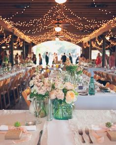 Indoor reception with fairy lights. Centrepieces with green-eyed roses, lisianthus, craspedia, lavender, and ranunculus