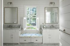 Welcoming beach style bathroom is fitted with rectangular beaded mirrors mounted to a white shiplap backsplash beneath frosted glass downlight sconces and above white beadboard washstands.