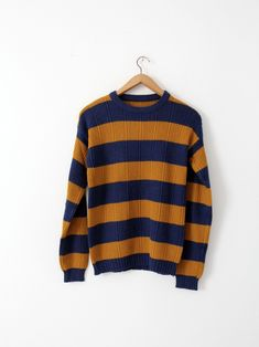 A 1970s vintage striped knit sweater. The ribbed knit crew neck sweater features bold blue and gold horizontal stripes. - blue and gold - acrylic or cotton blend - ribbed pattern - crew neck CONDITION