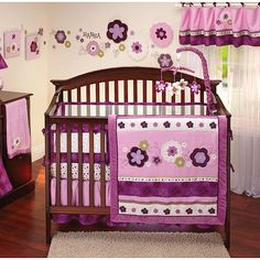 NoJo - Pretty in Purple 9pc crib Set Includes: comforter printed crib sheet solid crib sheet dust ruffle window valance diaper stacker and 3pc soft wallhanging. Beautiful floral motif with applique and embroidery. Colors are purple raspberry pink mauve and ivory with a touch of moss green. The printed sheet is a floral mix print on an ivory background solid sheet is in raspberry pink. Fits a standard size crib mattress 28