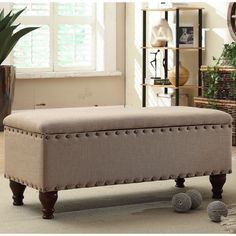 Seating, style and storage combine in this functional storage bench. Upholstered in a contemporary tan linen, this storage bench features decorative nail head trim as well as a safety hinged lid to protect fingers from injury.