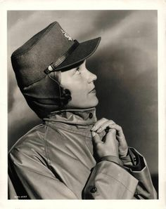 """1941- Volunteer of the Canadian Women's Army Corps models """"kepi"""" style cap and issue raincoat."""