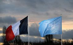 The flags of the U.N. and France fly as world leaders arrive for the COP21, United Nations Climate Change Conference, in Le Bourget, outside Paris, Monday, Nov. 30, 2015.