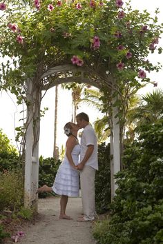 Barefoot bride and groom kiss beneath a flowered alter at this Florida beach wedding. Love her simple white tiered dress and the flower in her hair is a nice touch