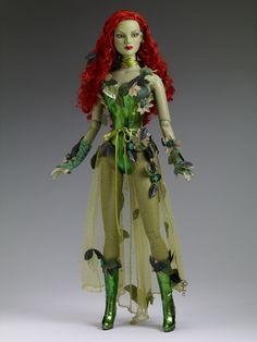"#Pin2Win DC Stars - 22"" Poison Ivy - $349.99 Dressed Tonner Character Figure™  American Model™ head sculpt  22"" American Model™ body  Wicked skin tone  Green inset eyes  Flame red rooted saran hair with attached faux leaves  Metallic green faux leather bodysuit with faux leaves  Green belt with attached glitter tulle over skirt with faux leaves  Green glitter tights  Green lace gloves  Green choker with faux leaves  Green faux leather boots with faux leaves trim  Green earrings - DC Comics"