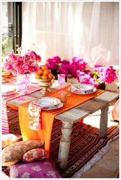 An old door turned table creates a fun and vibrant tablescape with pins and oranges by Camille Styles