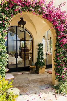 Arched entryway covered in greenery epitomizes the Mediterranean style entry