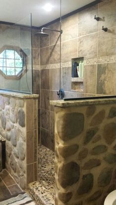 Rustic country stone shower with granite, glass, pebble rock shower floor, and double showerheads.