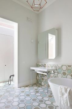Contemporary bathroom features blue and gray hex tiled floors lined with a nickel two leg washstand and a curved vanity mirror near an oval shaped tub.