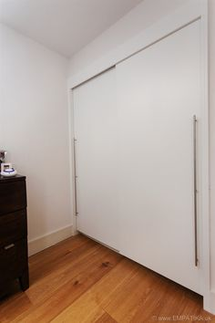 This is a couple of sliding wardrobes, contemporary style, made to measure in London, UK for private clients. They wanted sliding doors so that the doors did not hit their bedside table.  I love the long handles don't you?  See more at http://www.empatika.uk/gallery