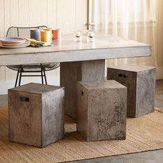 """GRAVITAS CEMENT DINING STOOL--OK, so what else would you call a sturdy stool made of granite stone powder and Portland cement mixed with natural jute fibers and water to make it manageable? Sleekly sculpted and cast with handy handholds, the neat near-cube can be used as seating or an extra table, indoors or out. Just so you know, it weights 39 lbs. Sealed rustic cement finish. 13-3/4""""W x 13-3/4""""D x 18""""H. Sold individually."""