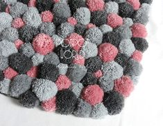 Tonos de gris son muy de moda ahora mismo. Había ilustrado este diseño con delicados pompones rosa. Esto le da el brillo de la alfombra necesaria y suma felicidad.  Este tipo de alfombra será perfecta para un dormitorio - para poner cerca de tu cama. La primera cosa que usted se sentirá en la mañana estarán suaves pompones. Este es un gran comienzo de un día!  Esta manta consiste en más de 200 pompones hechos a mano en algunas dimensiones.  Dimensiones: 80 cm x 50 cm / 32 x 20 Hay una…