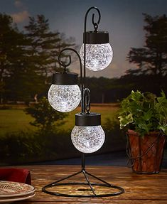 Add an enchanting glow to your porch or patio at night with this Solar Crackle Glass Ball Light Stand. Three glass balls are suspended from a black metal frame.