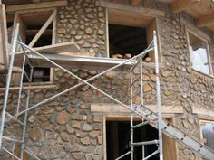 Cordwood construction. The wood is normally the size of firewood.  You can see the depth of the walls in the window frames.