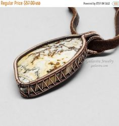 A gorgeous gemstone cabochon, with shades of yellow and white, with streaks of dark brown, is set in a simple copper wire wrap. Pendant is approximately 1 (25mm) wide and 2 1/8 (53mm) long. Pendant will be hung from your choice of necklace. Please select the desired type and length