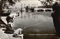 1960's. Boys fishing at the river Amstel in Amsterdam. In the background the Nieuwe Amstelbrug and Amstel Hotel. Photo MUVA. #amsterdam #1960 #Amstel #NieuweAmstelbrug #Amstelhotel