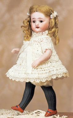 """SIMON & TINY SIMON & HALBIG ALL-BISQUE DOLL WITH LONG BLACK STOCKINGS. Marks: S & H 887. 6"""". Bisque swivel head on five-piece all-bisque body, brown sleep eyes, painted lashes, tapered brows, open mouth, upper teeth, blonde mohair wig, painted long black stockings and brown shoes, wears white crocheted dress over white batiste slip and panty ALL-BISQUE DOLL 6"""""""