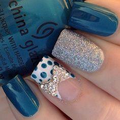 Bellas uñas en azul oscuro, una de ellas con brillos plateados, otra en blanco con lunares y un lazo con piedras cristalinas.