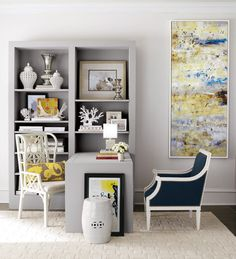 Grey, black and white office with pops of yellow. Love the abstract art and bookshelf styling.