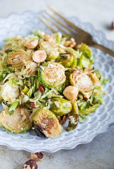 Brussels sprouts salad with hazelnuts, parmesan, and pomegranate molasses vinaigrette. Roasted Brussels sprouts and shaved raw Brussels sprouts are combined in this delicious, healthy and quick side dish!