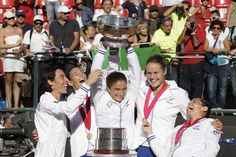 Italy's, from left, Francesca Schiavone, Flavia Pennetta, Sara Errani, Karin Knapp and Roberta Vinci celebrate with the trophy after winning the Fed Cup tennis final match against Russia, in Cagliari, Italy, Saturday, Nov. 3, 2013. Italy won a fourth Fed Cup title with a whitewash 4-0 victory over Russia on Sunday as seventh-ranked Sara Errani cruised past Alisa Kleybanova before Flavia Pennetta and Karin Knapp won the dead doubles rubber. (AP)