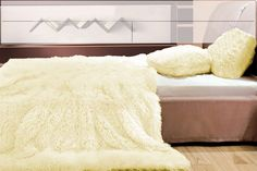 Chlpatá deka ako dekoratívna  prikrývka vanilkovej farby
