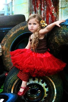 love the juxtaposition of cute girl in red tutu & truck tires