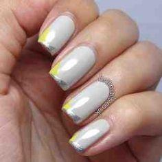 Uñas grises decoradas con líneas plateadas y amarillas en las puntas