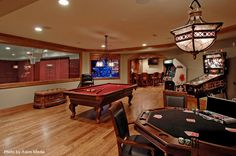 Huge traditional man cave with oak hardwood floors, a red pool table, a felt poker table, arcade games and a basketball court. Nothing more we need.