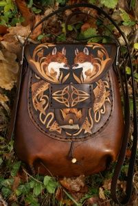 intricately carved medium sized pleated front bag with oak, foxes and salmon