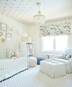 Neutral gender nursery features a ceiling clad in gold stars wallpaper, Coronata Star Wallpaper, lined with a PB Kids Dahlia Chandelier illuminating a nursing corner filled with a white terry cloth roll arm glider and ottoman placed in front of windows dressed in a butterflies roman shade.