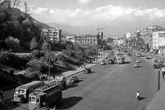 Micro, tranvías y automoviles por avenida Alameda, frente al cerro Santa Lucía de Santiago, c1950.
