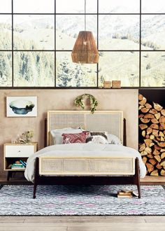 Cozy bedroom with a rattan pendant light, a vibrant rug, and a neutral headboard