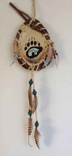 """Bouclier de protection """"Bear Spirit"""" - Zuni (Pintura), 14x57x19 cm por GrayWolf - Indian Héritage Arts Mandella Amérindien, patte d'ours et symbole de l'ours Zuni bouclier de protection peinture acrylique originale sur cuir, signée Entièrement naturel,le cuir est tendu sur un cercle de noisetier. Lanières de cuir ornées de perles de bois et de plumes naturelles Deux plumes stylisées en cuir sont accrochées de chaque côté. Diamètres: 14/19 cms hauteur totale 57 cms À l'origine, les shamans... Native American Crafts, American Indians, Bear Silhouette, Medicine Bag, Nativity Crafts, Dream Catcher, Jewelery, Cowgirls, Deco"""