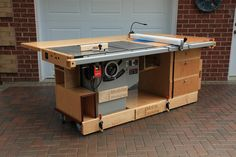 EKHO Mobile Workshop Front View showing cabinet saw, router table, folding outfeed table, workbench, 3 storage drawers, casters, stabilizer clamps.